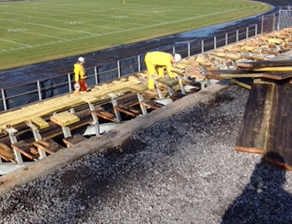 Workers remove the benches in the east side bleachers at Richardson Stadium